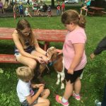 Child petting goat while two others look on.
