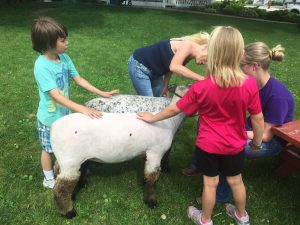 Children petting pet sheep.